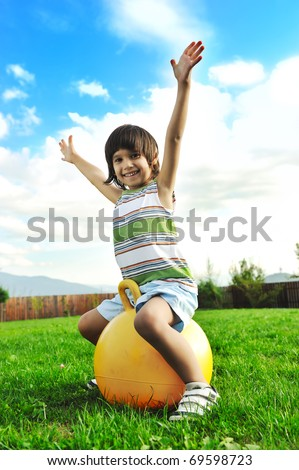Little happy boy playing with big ball and jumping with wide opened arms in air