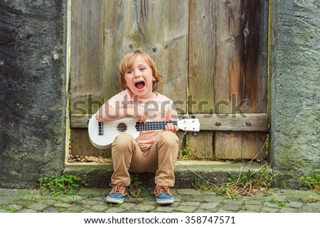 Little happy boy plays his guitar or ukulele - stock photo
