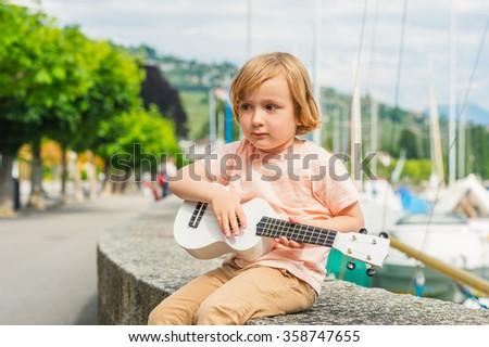 Little happy boy plays his guitar or ukulele - stock photo
