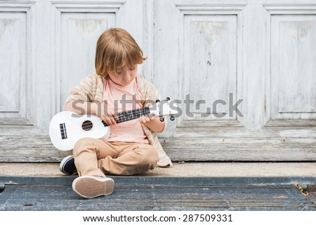 Little happy boy plays his guitar or ukulele, sitting by the wooden door outdoors - stock photo