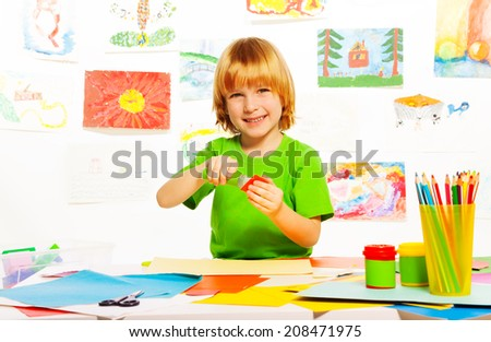 Little happy Caucasian blond boy glue color cardboard with glue stick in the room with images on background - stock photo