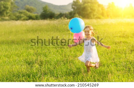 little happy cheerful girl running around playing and having fun with balloons in the summer on the nature - stock photo