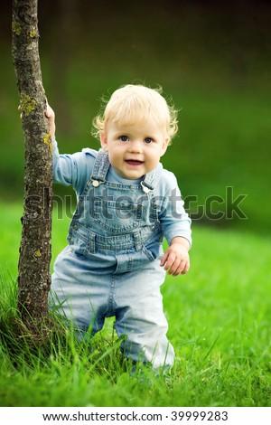 little happy child near the tree - stock photo
