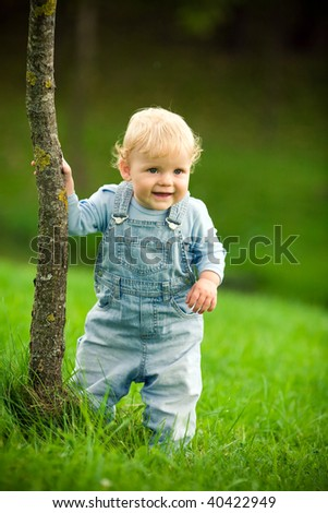 little happy child near the tree - stock photo