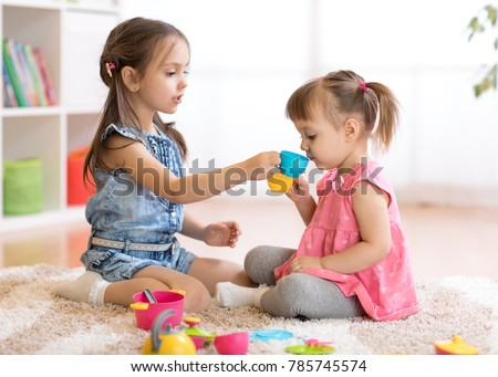Little Happy Children, Cute Kids Girls Play With Plastic Toy Kitchen On  Floor At Home