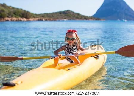 Little happy cute girl enjoy kayaking in the clear blue sea