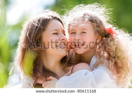 Little happy daughter and her young beautiful mother, both smiling. Nature background. - stock photo