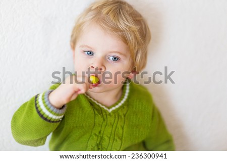 Little happy funny kid boy of one year old eating lollipop indoor