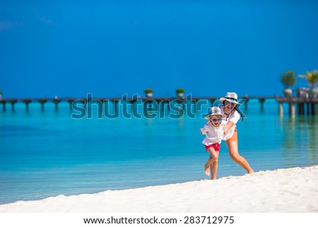 Little happy girl and young mother during beach vacation