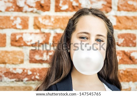 Little Happy Girl Blowing a Chewing Gum over a Brick Wall - stock photo