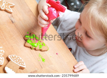 Little happy girl decorates Christmas gingerbread cookies using red glaze, selective focus  - stock photo