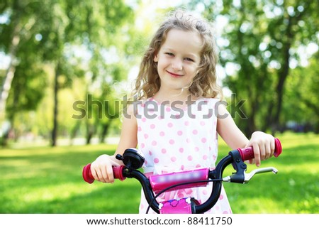 Little happy girl having fun in green summer park - stock photo