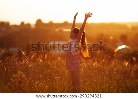 Little happy girl in a field on summer evening - stock photo