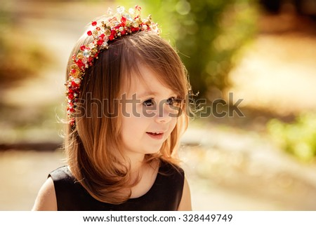 Little happy girl in black-red dress - stock photo