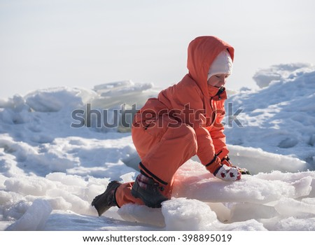 Little happy girl in orange jacket and snow pants playing with ice at frozen Baltic seashore