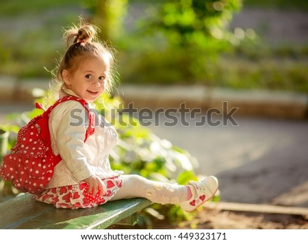 Little happy girl in white-red dress - stock photo
