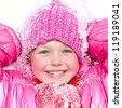 Little happy girl in winter pink hat in snow. - stock photo