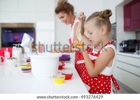 little happy girl is preparing cup cakes, muffins or pie on the kitchen at home. Daughter of 5 years old cooking