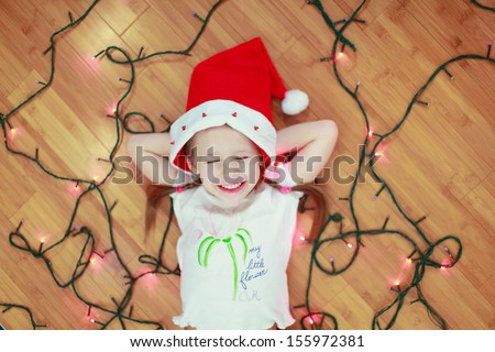 Little happy girl lies among the multi-colored lights on a wooden floor - stock photo