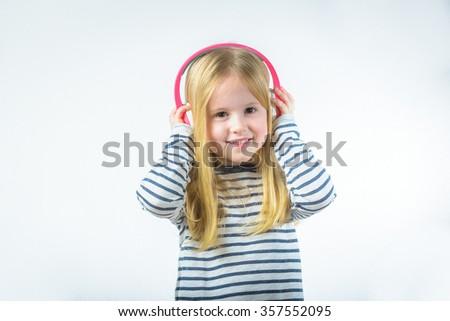 Little happy girl listening music on headphones - stock photo