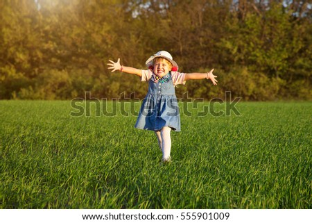 Little happy girl on the meadow in summer day. Child