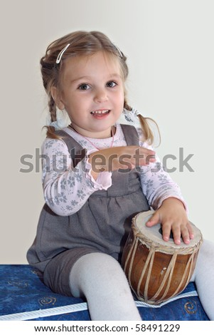 Little happy girl playing african drum and singing