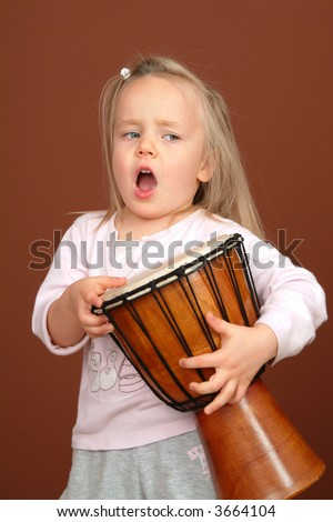 Little happy girl playing african drums and singing