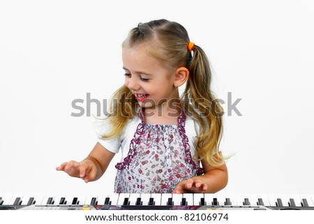 Little happy girl playing on a keyboard instrument. - stock photo