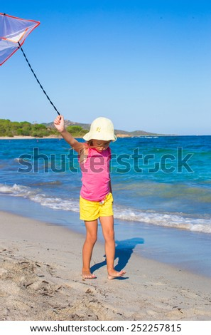 Little happy girl playing with flying kite during tropical beach vacation - stock photo