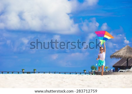 Little happy girl playing with flying kite on tropical beach - stock photo