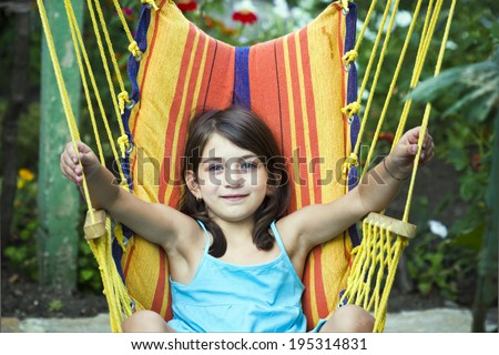 Little happy girl relaxing in hammock - stock photo