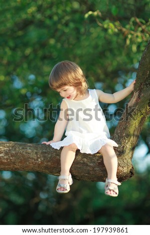 little happy girl sitting on the tree