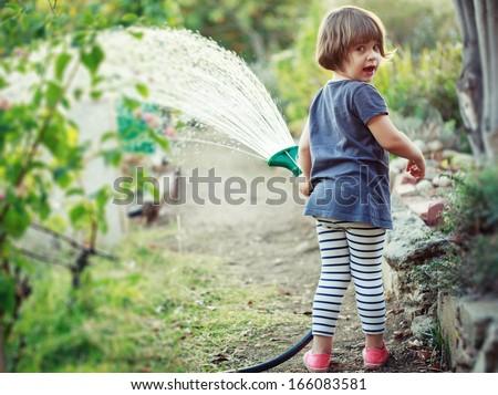 Little happy girl watering garden - stock photo