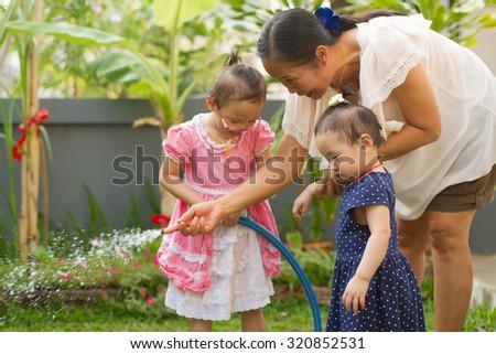 little happy girl watering in garden - stock photo