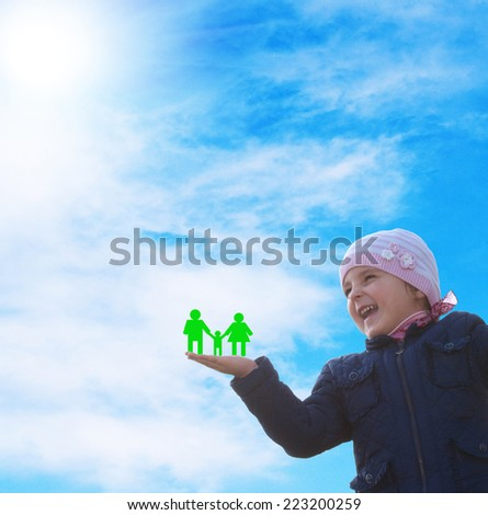 Little happy Girl with paper family on hand - stock photo