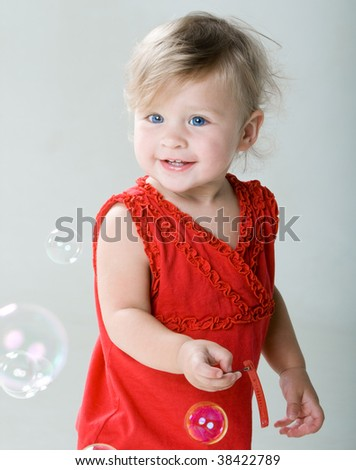 Little happy girl with soap bubbles