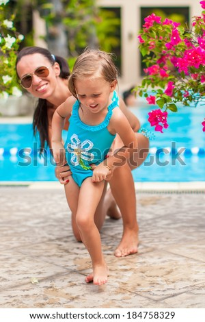 Little happy girl with young mother have fun near open-air pool - stock photo