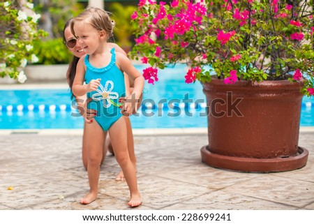 Little happy girl with young mother have fun near pool - stock photo