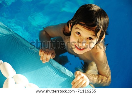 Little happy kid in the pool - stock photo