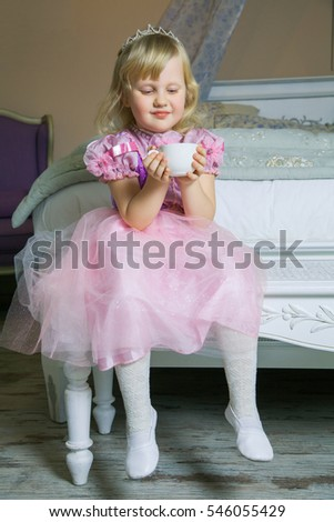 Little happy princess girl in pink dress and crown in her royal room sitting on chair and holding cup of drink.