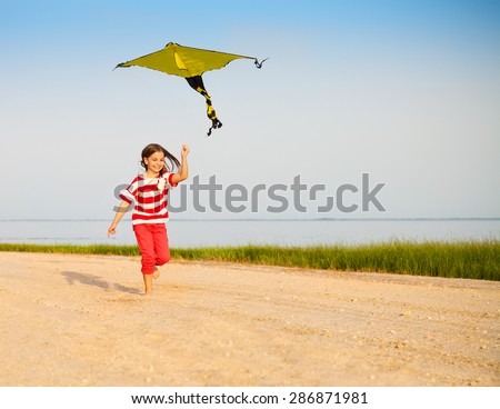 Little happy running girl with flying kite on beach at sunset - stock photo