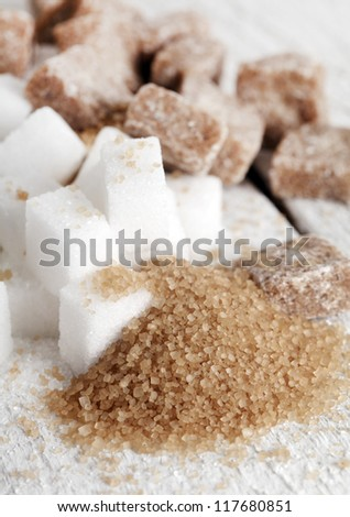 Little heap of white and brown sugar cubes on a white wooden surface - stock photo
