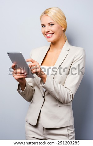 Little helper in her work. Confident young businesswoman working on digital tablet and smiling while standing against grey background - stock photo