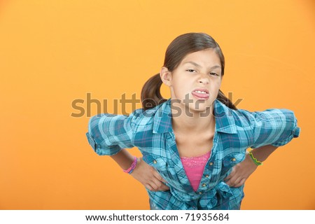 Little Hispanic girl with hands on hips sticks out her tongue - stock photo