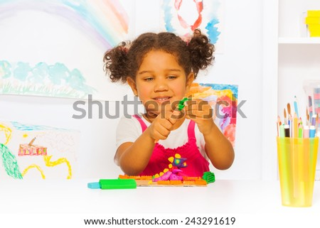 Little Hispanic looking girl play with plasticine