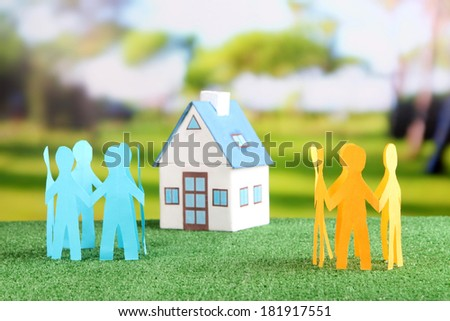 Little house and paper people on green grass, on bright background - stock photo