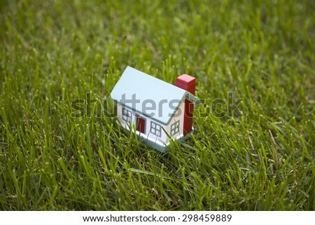 Little house on green grass  - stock photo