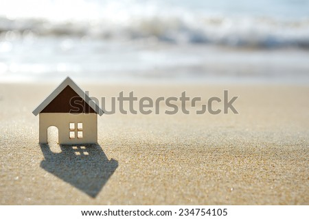 little house on the sand beach near sea - stock photo