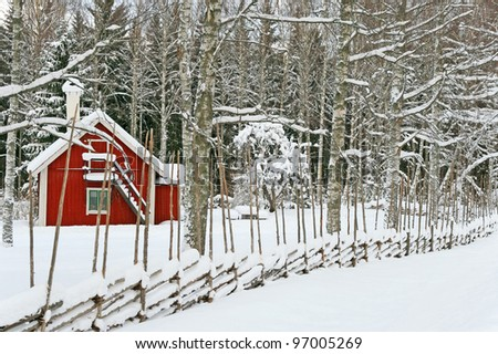 Little house painted in traditional Swedish red and brown colors, covered by snow. - stock photo
