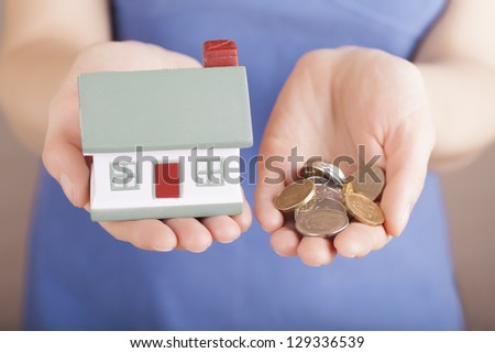 Little house toy and money in woman's hands - stock photo